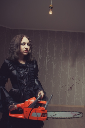 Pretty cute red-eyed girl with bloody chainsaw posing in the empty room photo