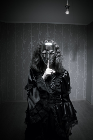 Girl in mask dressed in black old-fasioned clothes posing in the empty room photo