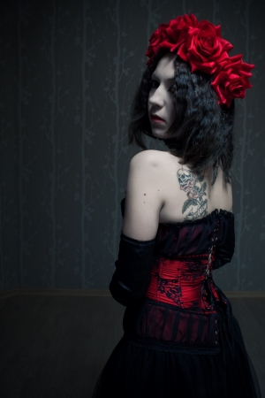 red corset: Pretty gothic girl in red corset with flowers on her head posing in the empty room