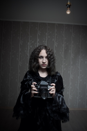 Cute red-eyed gothic girl in black old-fashioned dress with camera in the empty room photo