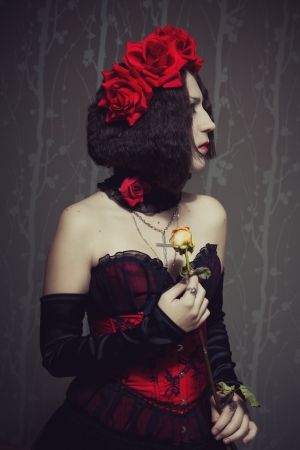 Beautiful sad girl with  rose standing in the empty room photo