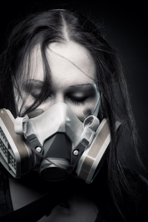 Pretty girl in gasmask posing over dark background photo