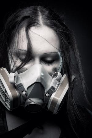 gasmask: Pretty girl in gasmask posing over dark background