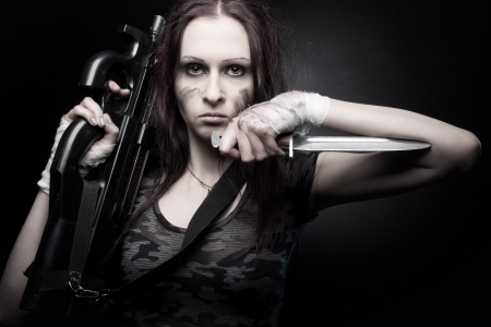 Pretty young woman with fn p90 and knife posing over dark background