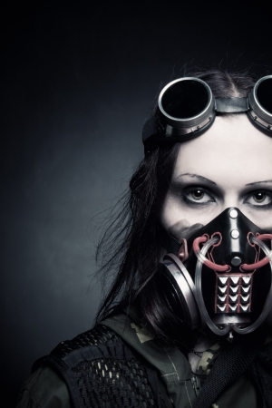 post apocalypse: Portrait of post apocalyptic girl in gas mask over dark background Stock Photo