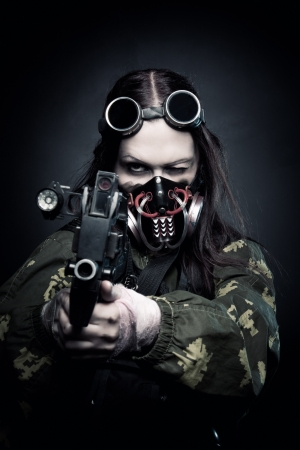 post apocalypse: Military girl in gasmask with fn p90 posing over dark background Stock Photo