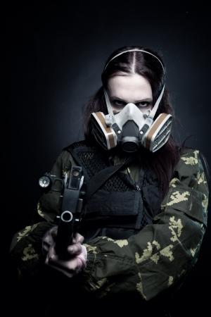 gasmask: Ragazza militare in maschera antigas con fn p90 posa su sfondo scuro