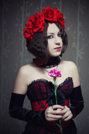 Cute red-eyed girl with roses on her head and carnation in her hands standing in the empty room photo