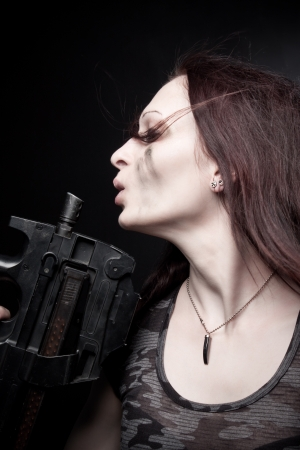 Pretty young woman with fn p90 and knife posing over dark background photo