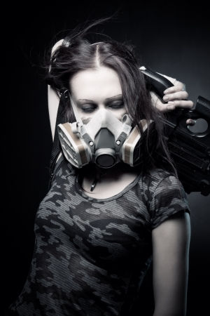 gasmask: Military girl in gasmask with fn p90 posing over dark background Stock Photo