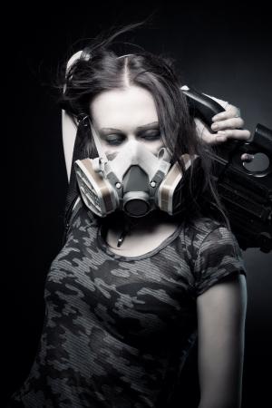 gasmask: Ragazza militare in gasmask con fn p90 posa su sfondo scuro Archivio Fotografico