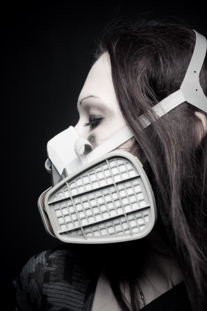 Pretty girl in respirator posing over dark background photo