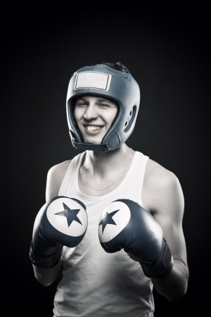 dauntless: Young boxer in gloves posing over dark background