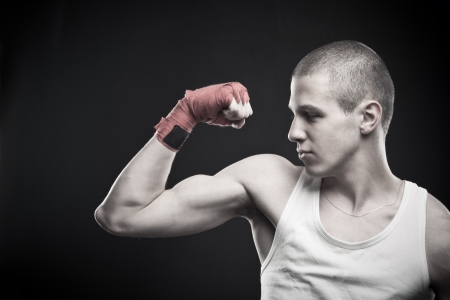 dauntless: Young strong man showing his biceps over dark background.