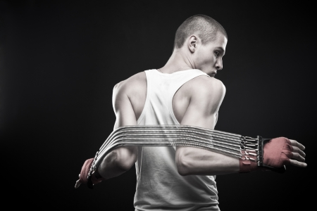 dauntless: Young sportsmen stretching expander over dark background