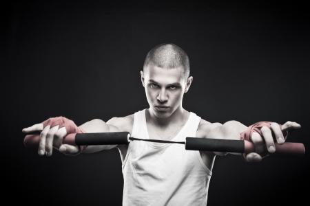 dauntless: Young man posing with  nunchaku over dark background