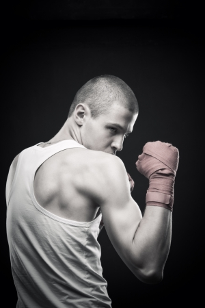 Young agressive boxer posing over dark background Stock Photo - 17383343