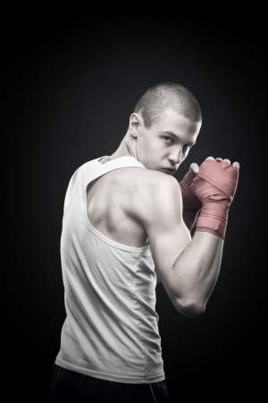 Young agressive boxer posing over dark background Stock Photo - 17383338