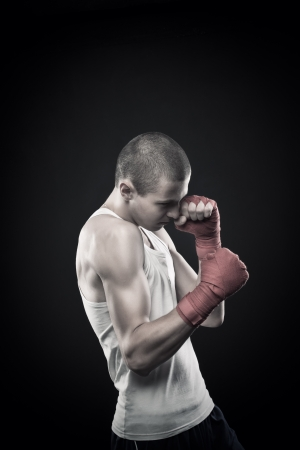 Young agressive boxer posing over dark background Stock Photo - 17383340