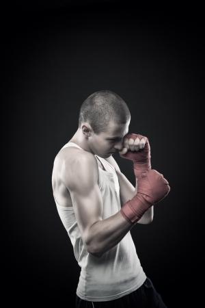dauntless: Young agressive boxer posing over dark background