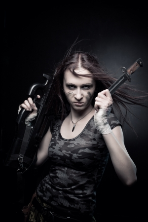 Pretty young woman with fn p90 and knife posing over dark background Stock Photo - 17383342