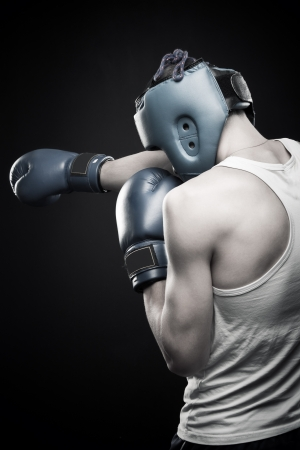 dauntless: Young aggressive strong man boxing over dark background  Rear view
