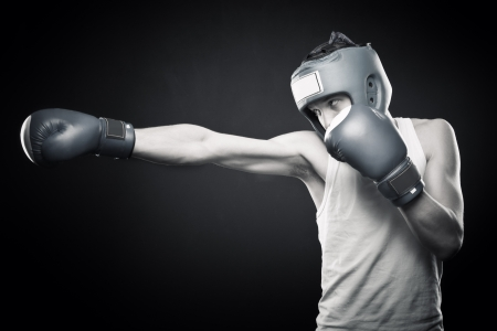 Young aggressive strong man boxing over dark background 스톡 콘텐츠