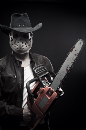 American maniac with chainsaw in mask and cowboy hat posing over dark background Stock Photo - 17347192