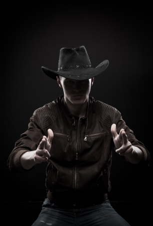 Brutal macho in cowboy hat posing over dark background