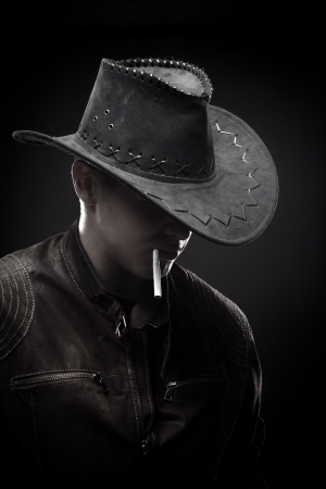 manly man: Brutal macho in hat with cigarette over dark background