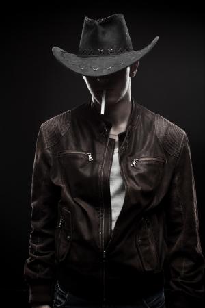 vaquero: Vaquero fresco en la chaqueta con el cigarrillo sobre fondo oscuro