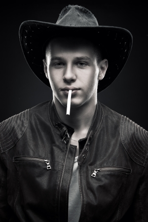 Portrait of handsome cool cowboy with cigarette over dark background photo