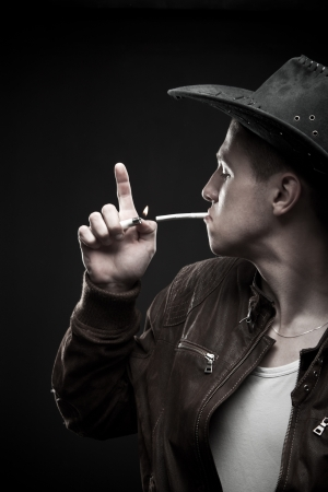 Young man  in hat posing over dark background with cigarette lighter