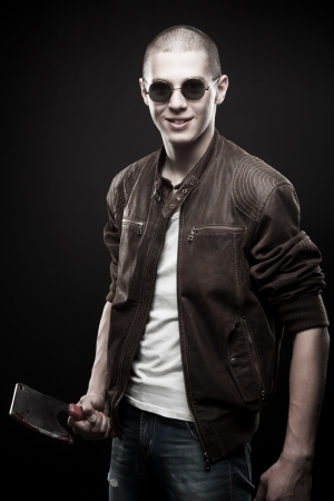 Young man in sunglasses with bloody chopper posing over dark background photo