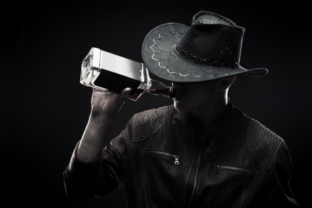 Brutal macho in hat drinking whisky over dark background Stock Photo - 17370126