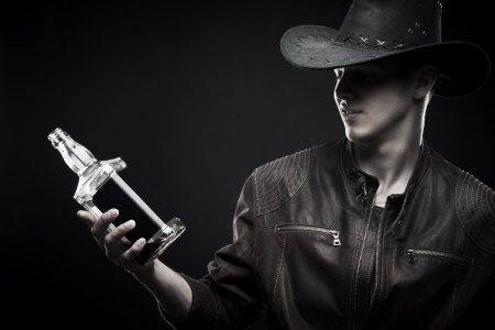 Macho in cowboy hat with bottle of whisky posing over dark background Stock Photo - 17370128