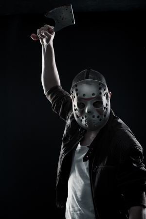 Horrible maniac with bloody chopper posing over dark background Stock Photo - 17450516