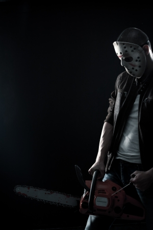 maniac: Horrible maniac in mask with bloody chainsaw posing over dark background Stock Photo
