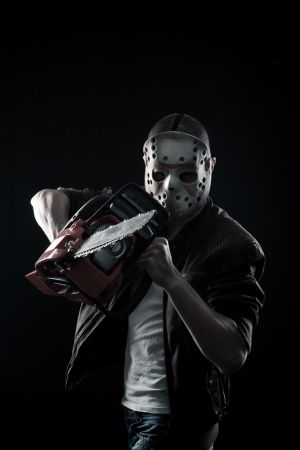 Horrible maniac in mask with chainsaw posing over dark background photo
