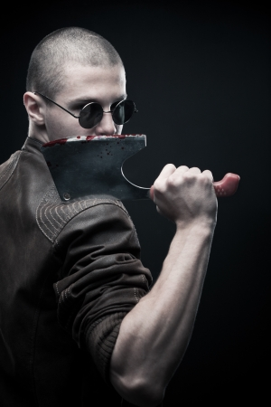 Horrible maniac with bloody chopper posing over dark background Stock Photo - 17450517