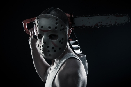 Horrible maniac with bloody chainsaw posing over dark background photo