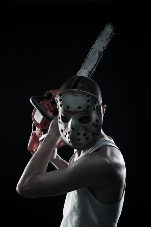 Horrible maniac with bloody chainsaw posing over dark background Stock Photo - 17450502