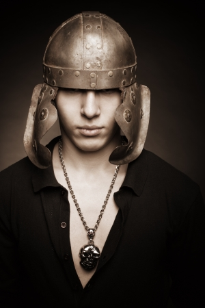 Portrait of serious man in roman helmet over dark backgorund Stock Photo - 17480199