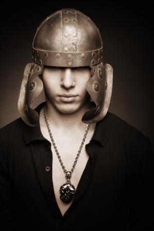 Portrait of serious man in roman helmet over dark backgorund Stock Photo - 17480199