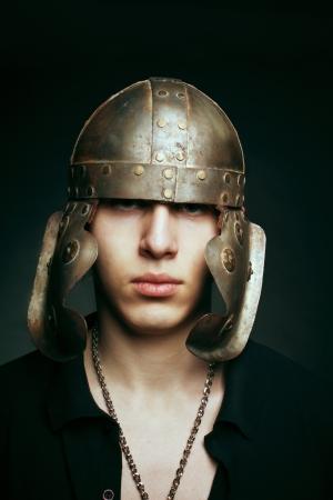 Portrait of young serious man in roman helmet over dark Stock Photo - 17480198