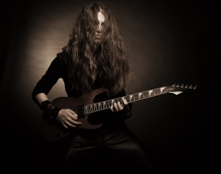 Brutal cool metal guitarist playing the guitar over dark background photo