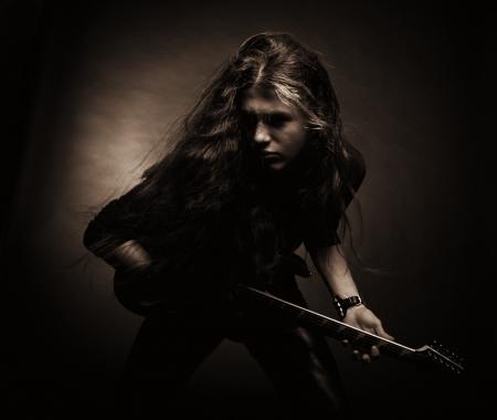 어두운 배경 위에 전기 기타 포즈와 헤비 메탈 기타리스트 스톡 콘텐츠 - 17480194