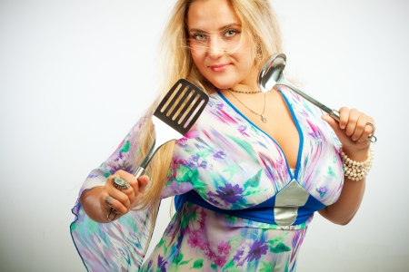 Pretty young woman with ladle and spatula posing over white Stock Photo - 17605553