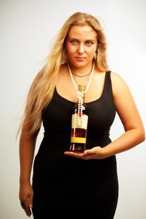 Sexy young woman posing with bottle of rum over white backgorund Stock Photo - 17605548