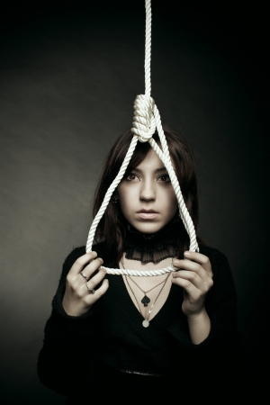 Sad girl with gallows over dark background photo